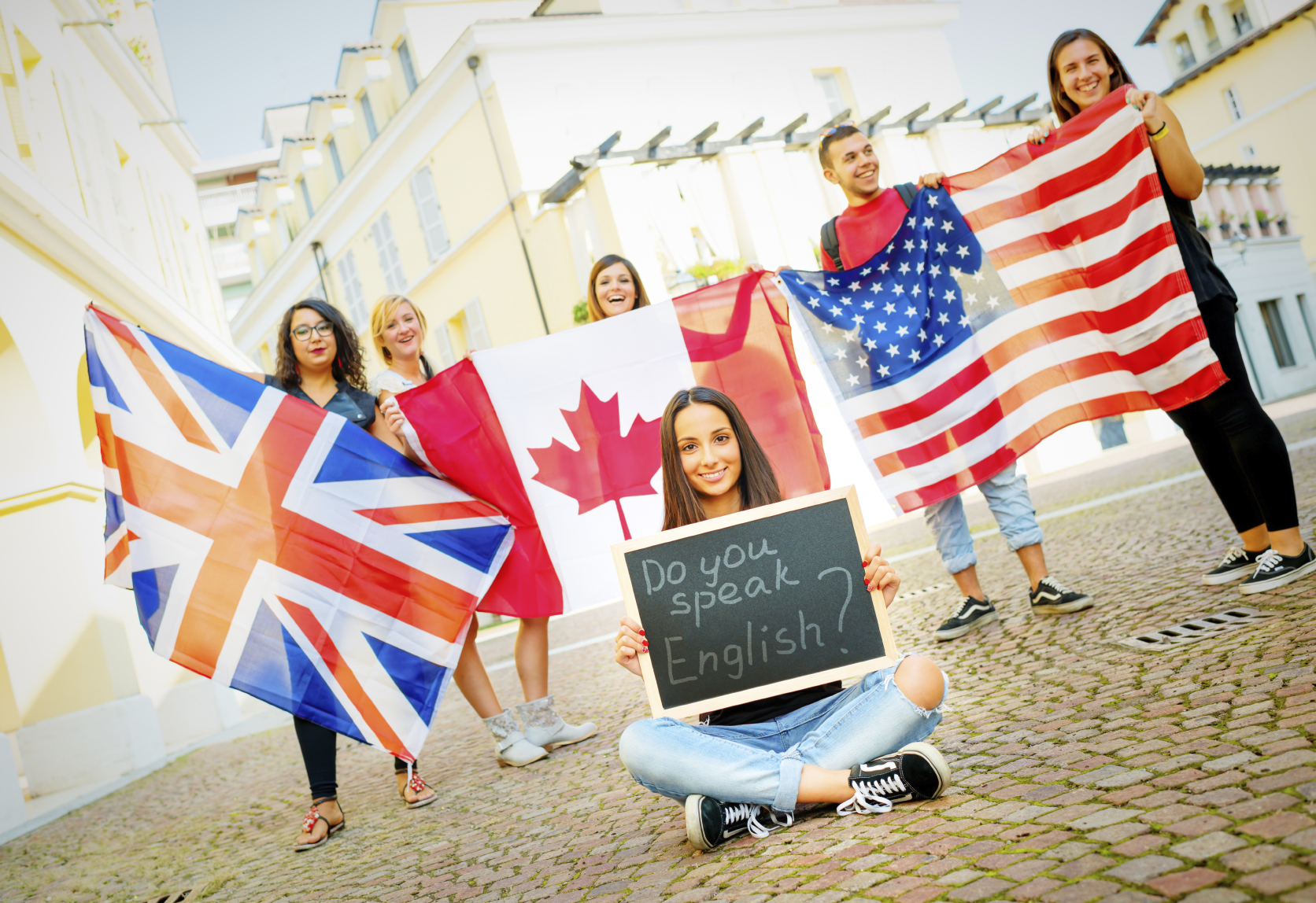 Image of College students learning English with flags and blackboard, outdoors.
