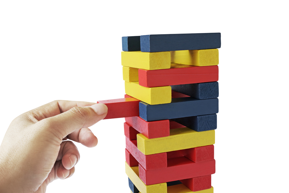 Image of a male hand placing wooden block on a tower
