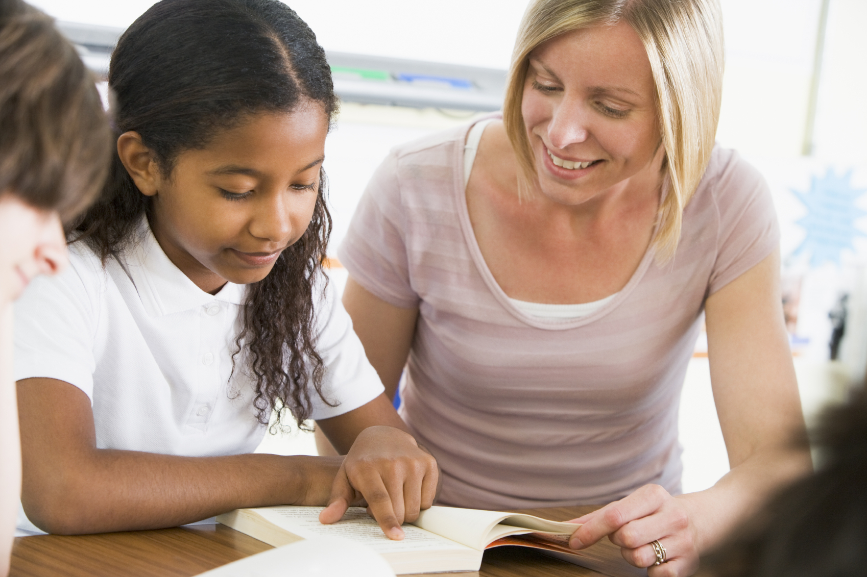 Image of a Schoolgirl and teacher reading a book in class