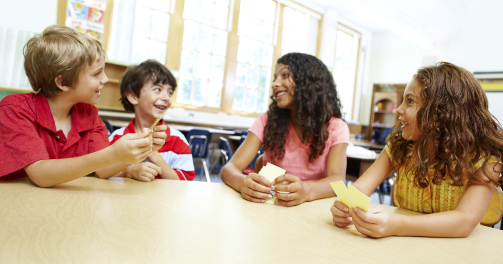 Image of Four young children playing cards in their classroom together