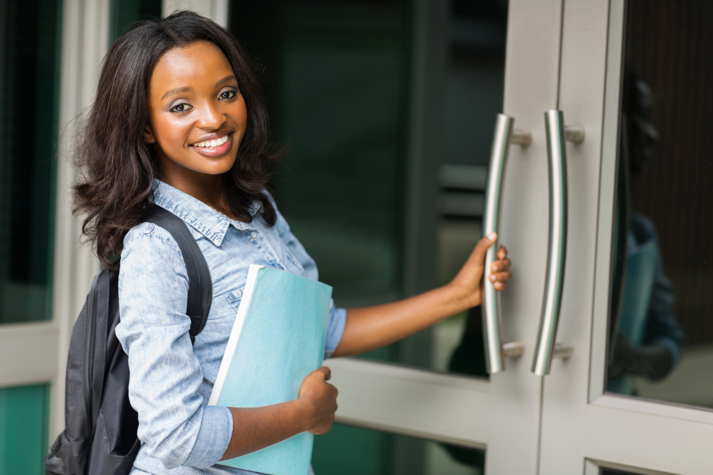 Image of smiling african female college student going to lecture hall