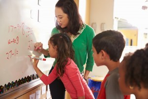 Students and teacher doing math at the whiteboard