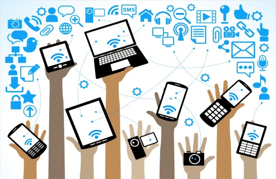 Hands holding various technology devices