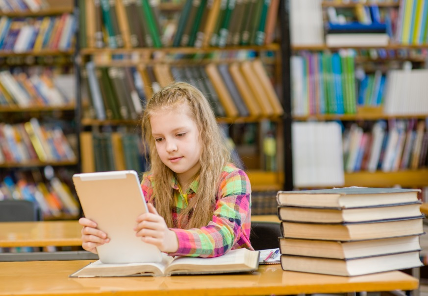 Female student reading from a tablette in a library