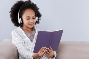 Girl reading with headphones on
