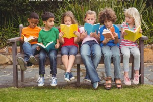Primary students reading on a bench