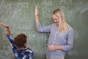 Teacher and student give a high-five with the alphabet on the blackboard