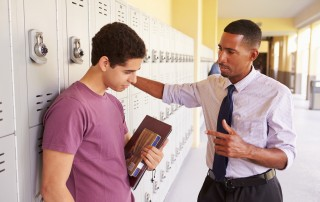 teenage boy speaking with teacher in front of lockers