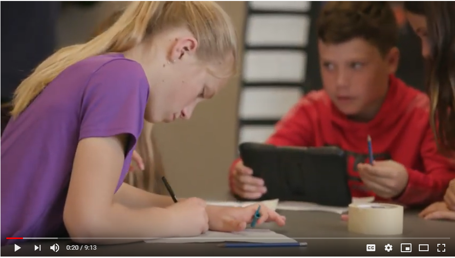 Still from the Accessible texts video series showing a female student in the foreground writing on paper and a male student in the background using an ipad.
