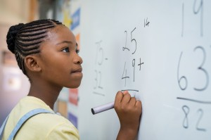 Young girl stands at white board with marker in hand, pondering a math equation.